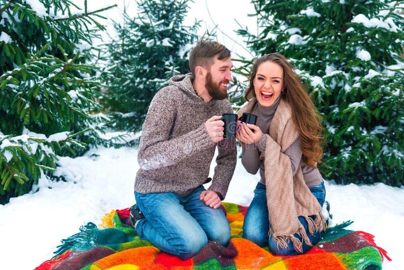 Winterpaare, die Becher gegen Weihnachtsbaum halten lizenzfreies stockbild