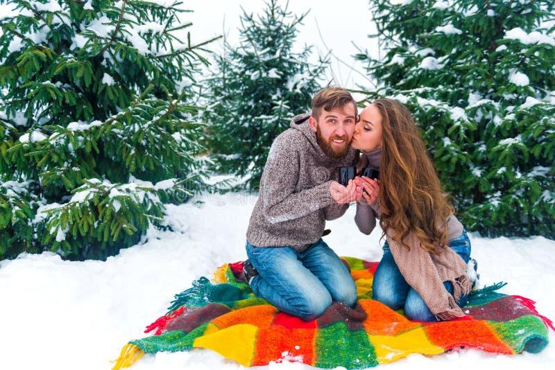 Winterpaare, die Becher gegen Weihnachtsbaum halten stockfotos