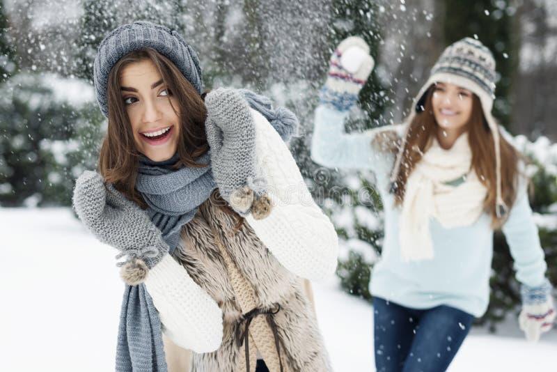 Winterpaare, die Spaß haben, draußen zu spielen im Schnee stockbilder