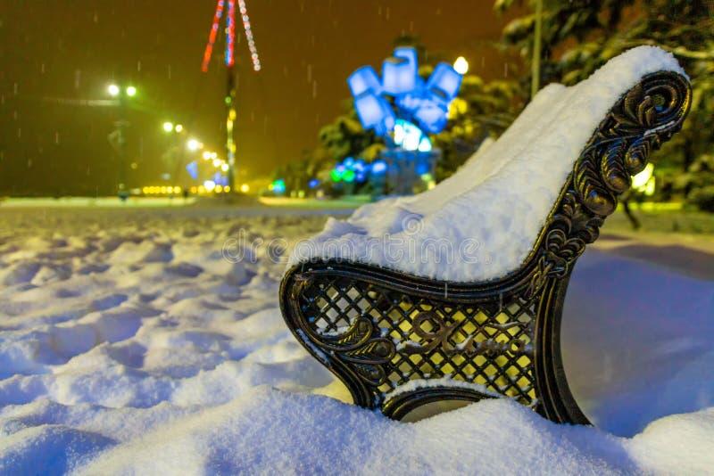 Winterpark abends schneebedeckt mit einer Reihe von Lampen Aussicht auf die Bank und glänzende Laterne durch Schnee Winternacht lizenzfreies stockbild