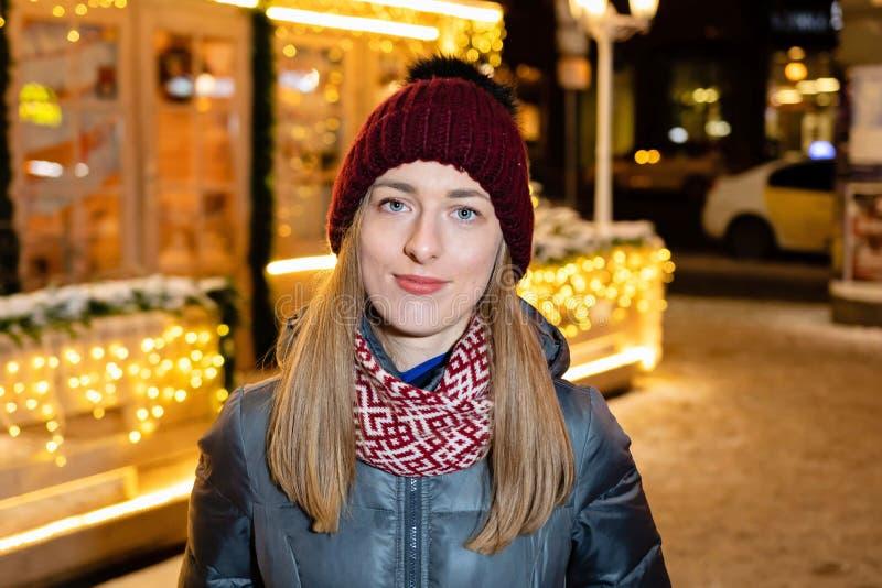Winterporträt der glücklichen jungen Frau, die in die schneebedeckte Stadt verziert für Weihnachten und Neujahrsfeiertage geht stockfotos