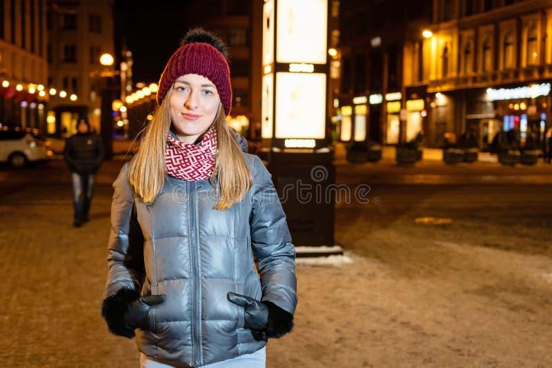 Winterporträt der glücklichen jungen Frau, die in die schneebedeckte Stadt verziert für Weihnachten und Neujahrsfeiertage geht lizenzfreies stockbild