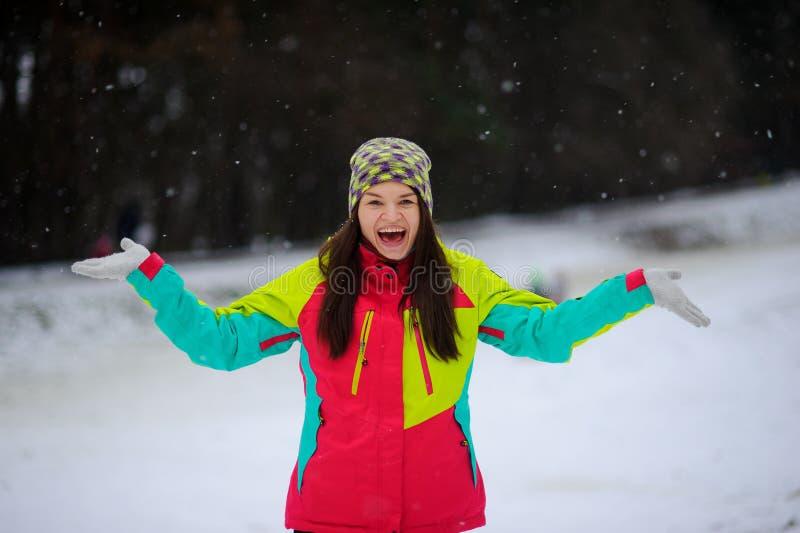 Winterporträt der jungen Frau im hellen Skianzug und in einer Strickmütze lizenzfreie stockfotografie