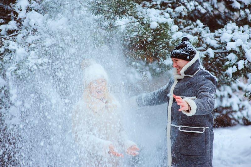 Winterporträt des glücklichen Paars, das Los Spaß hat und den Schnee im Freien wirft stockbild
