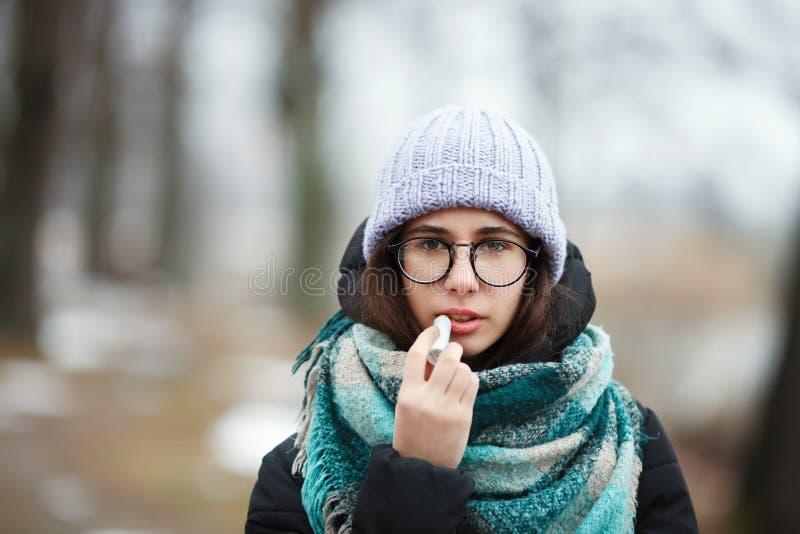 Winterporträt des jungen netten schlendernder Winter Forest Park Brunette-Mädchens Anwenden des hygienischen Lippenstifts lizenzfreies stockfoto