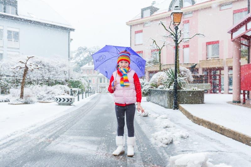Winterporträt eines netten kleinen Mädchens unter den Schneefällen stockfotos
