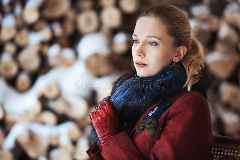Winterporträt von Blondinen auf Brennholzhintergrund lizenzfreie stockfotos