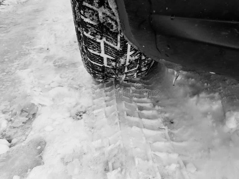 Winterreifen mit den Bahnen nah herauf Schuss auf dem Schnee in Schwarzweiss lizenzfreie stockfotografie