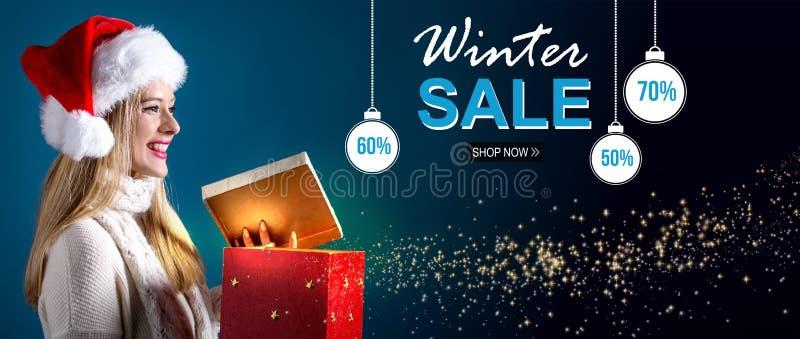 Winterschlussverkaufmitteilung mit der Frau, die eine Geschenkbox öffnet lizenzfreies stockbild