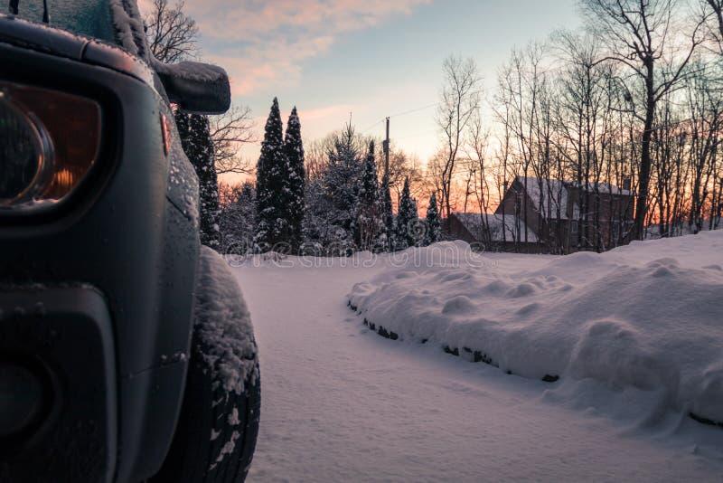 Winterschneedecken Fahrstraße und Fahrzeug auf einem ruhigen Morgen an der Dämmerung stockbilder