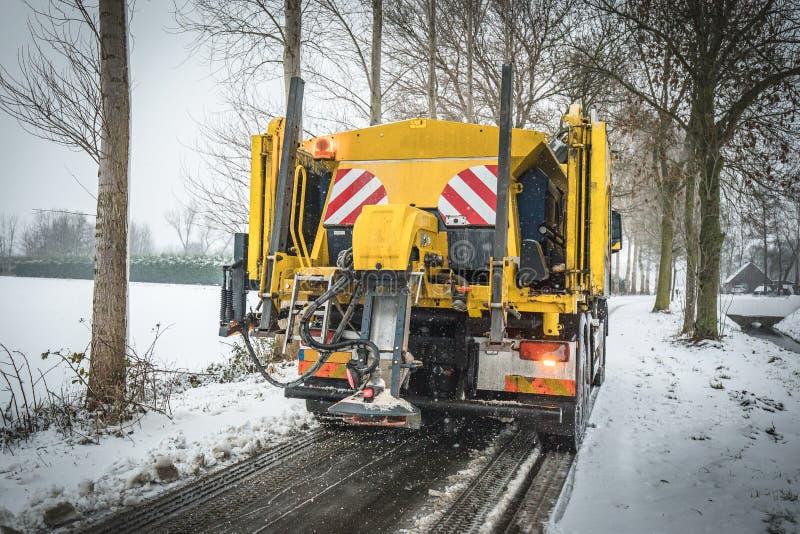 Winterservice-LKW-Salzstreuung auf Straße stockfoto