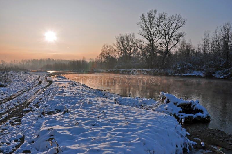 Wintersonnenaufgang über schneebedecktem Fluss stockfotografie