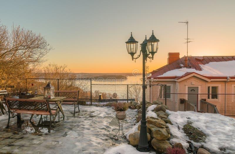 Wintersonnenuntergang über dem See und dem malerischen alten Hof im städtischen Dorf von Finnland stockbild