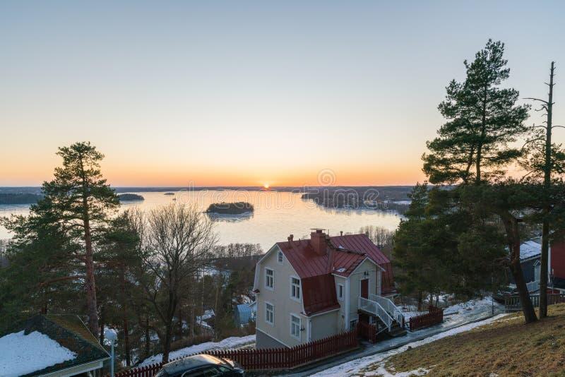 Wintersonnenuntergang über dem See und dem malerischen alten Hof im städtischen Dorf von Finnland stockbilder