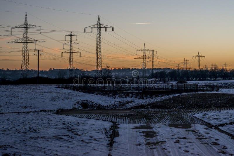 Winterstarkstromleitungssonnenuntergang-Sonnenaufgangdämmerung 3 des Stahlturmlandschaftschnees weiße stockfotografie