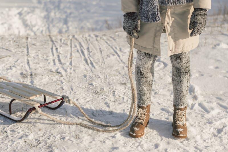 Winterstiefel auf Schnee nahe Schlitten mit Seil stockfotografie