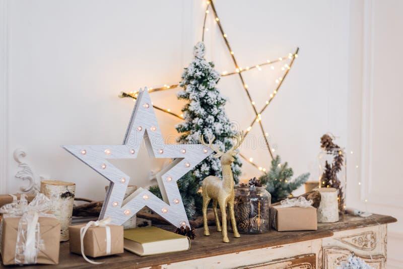 Winterstillleben mit Weihnachtsdekorationen spielen Rotwild, Stern und Geschenkboxen auf hellem Hintergrund Weichzeichnung, verwi stockbilder