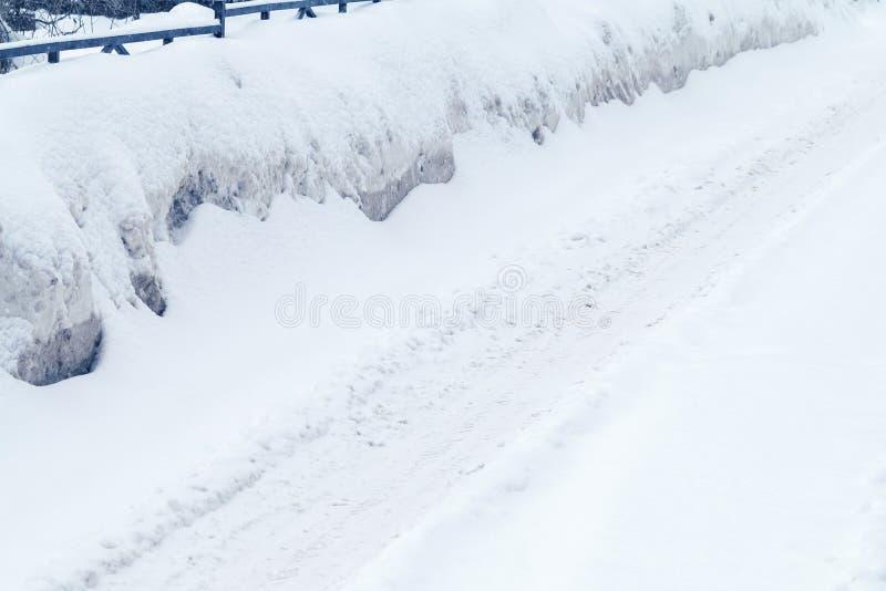 Winterstraße bedeckt mit Schnee, Antriebe auf der Seite der Straße lizenzfreies stockfoto