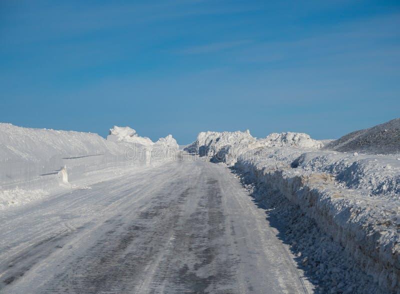 Winterstraße macht seine Weise durch die Schneeantriebe mehr als zwei Meter hoch in Altai, Russland lizenzfreies stockbild