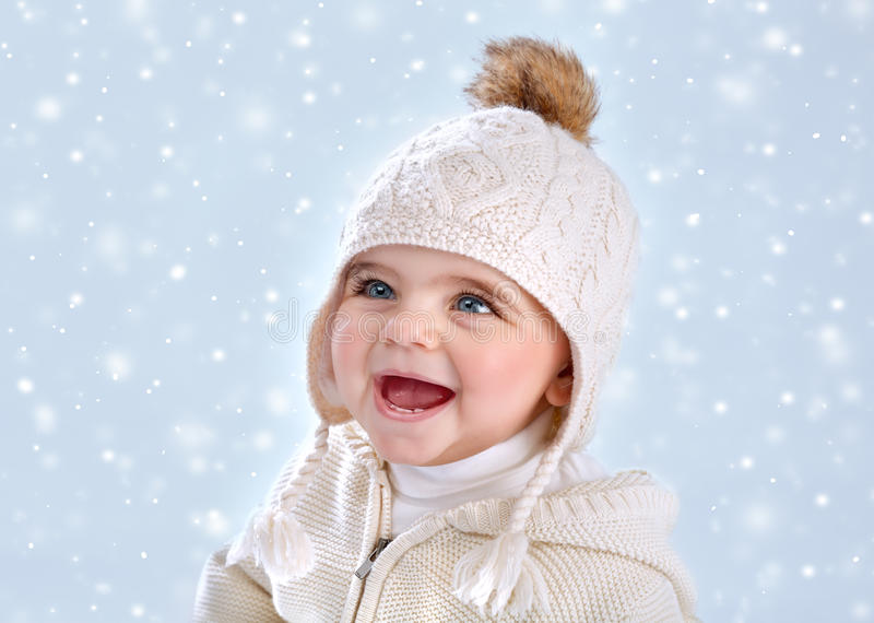 Wintertime baby fashion. Portrait of cute little baby girl wearing warm stylish hat on blue snowy background, snow falling, winter season, happy child concept stock photo