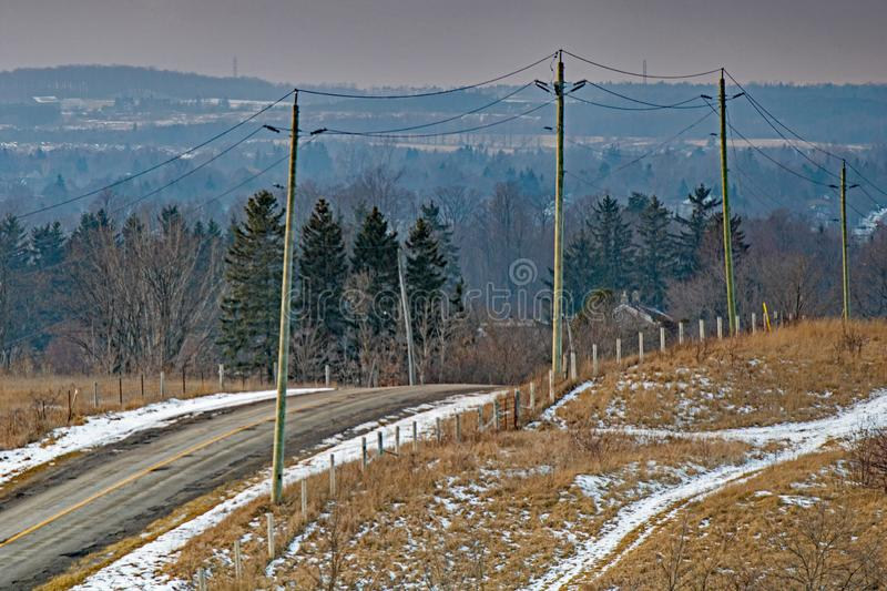Wintertime On A Back Road In A Rural Setting. A dusting of snow covers the ground on this country road in a rural setting. The location is near the town of royalty free stock image
