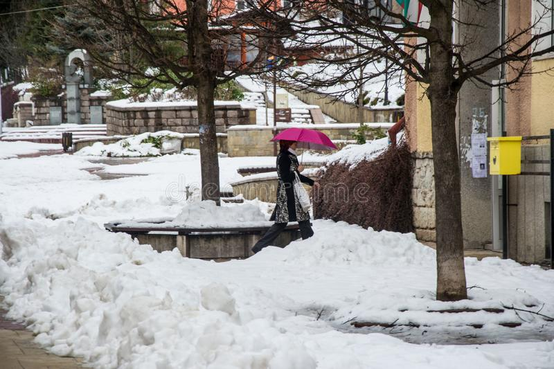 Smolyan ,Bulgaria - January 28, 2019 - Street in the city of Smolyan, woman holding an umbrella, snow-covered ground, wintertime. Wintertime in the city, a woman royalty free stock images