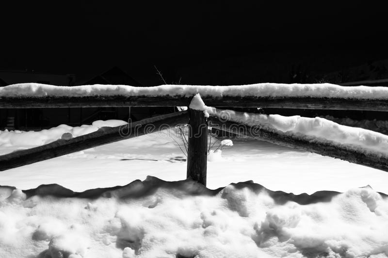 Wintertime fallen snow on wooden fence motif at night royalty free stock photos