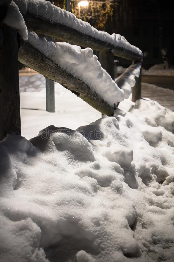 Wintertime fallen snow on wooden fence motif at night royalty free stock photography