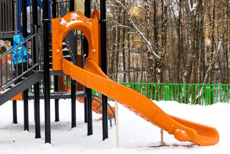 wintertime Liten unge som uppför trappan kör till glidbanan på leken royaltyfria foton