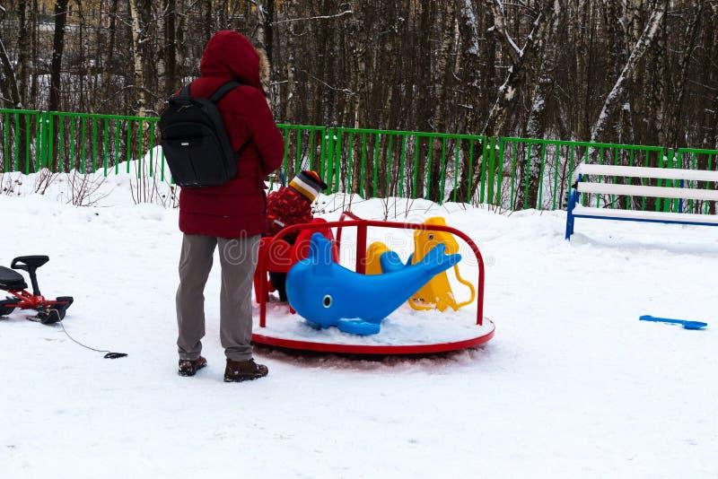 wintertime Mamma som håller ögonen på den lilla ungen glidning glidbanan på plommonerna royaltyfri fotografi