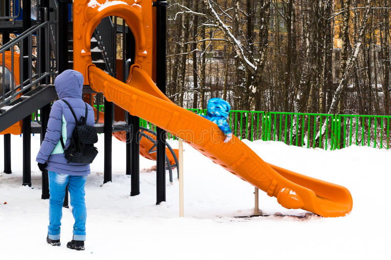Wintertime. Mom watching little kid sliding the slide on the playground royalty free stock image