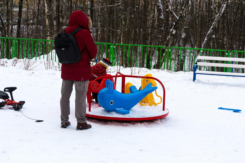 Wintertime. Mom watching little kid sliding the slide on the playground royalty free stock photography