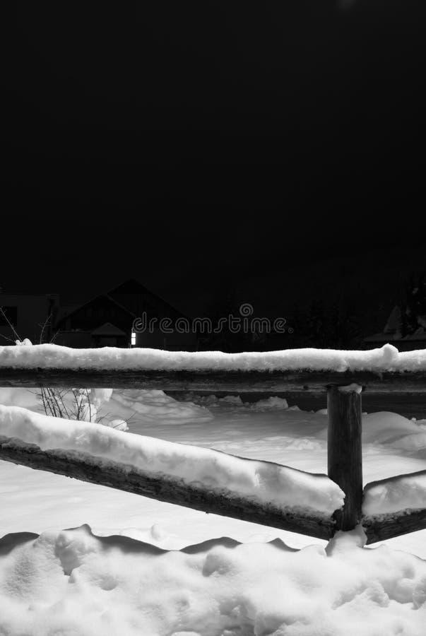 Wintertime spadać śnieg na drewnianym płotowym motywie przy nocą fotografia royalty free
