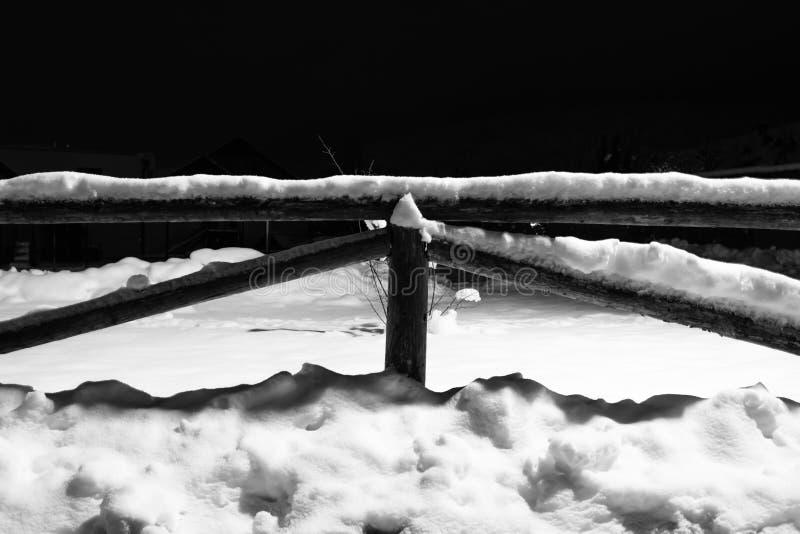 Wintertime spadać śnieg na drewnianym płotowym motywie przy nocą zdjęcia royalty free