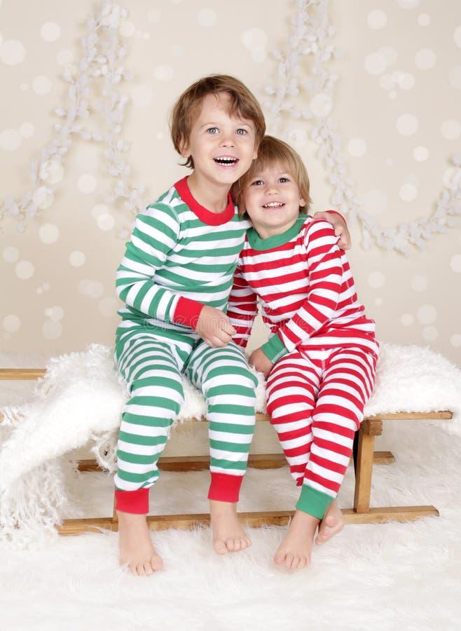 Winterurlaube: Lachende glückliche Kinder in Weihnachtspyjama-Schlitten I stockfotografie