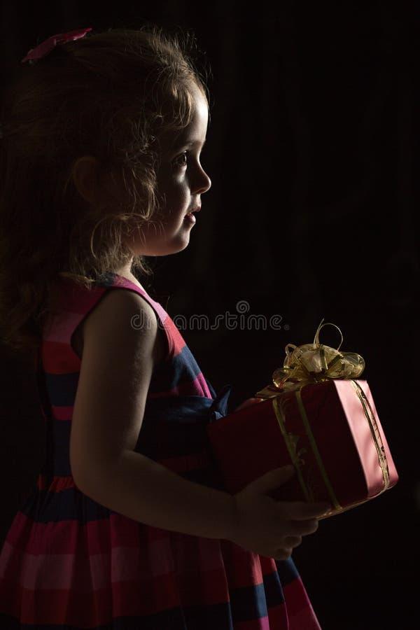 Winterurlaube - Schattenbild eines schönen kleinen Mädchens mit Geschenk über schwarzem Hintergrund lizenzfreie stockfotografie