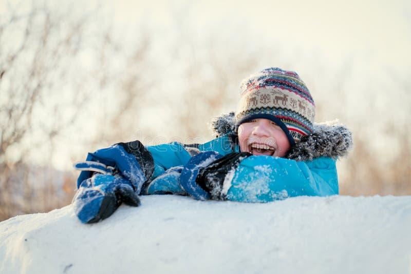 winterwear的笑愉快的孩子,当使用在随风飘飞的雪时 免版税库存照片