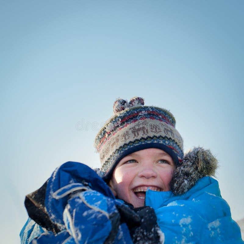 winterwear的笑愉快的孩子,当使用在随风飘飞的雪时 库存图片