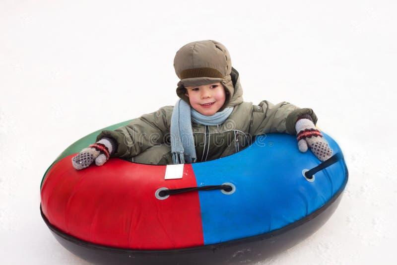 Winterweg, Junge reitet einen Schnee-Schläuche stockbild