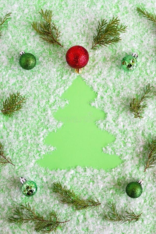 Winterzusammensetzung mit Weihnachtsbaum, Tannenzweige andChristmas Dekorationen auf einem grünen Hintergrund mit künstlichem Sch lizenzfreies stockfoto