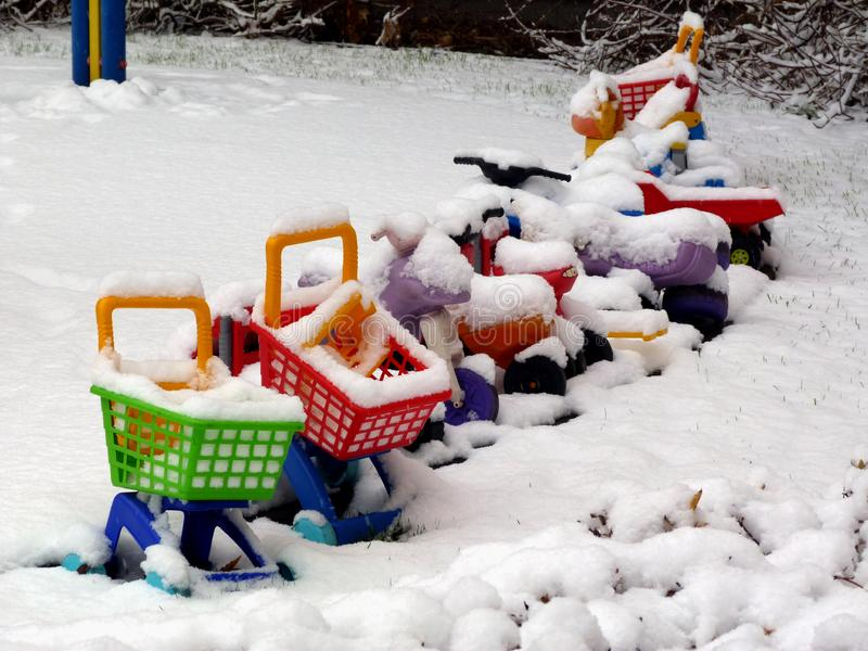 Wintry court yard scene with child toys and play equipment. Wintry court yard scene with snow covered colorful plastic child toys and equipment under snow and royalty free stock image