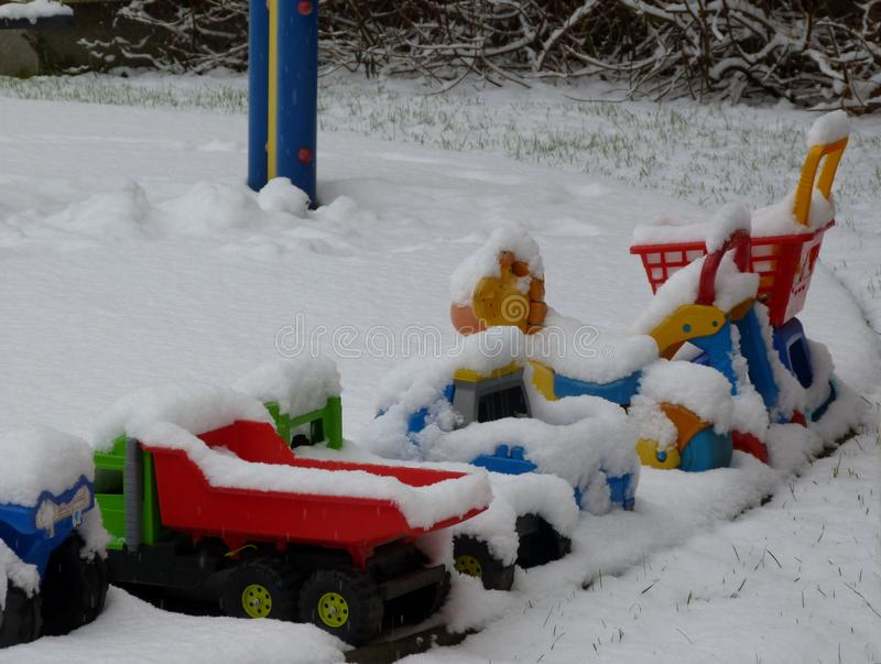 Wintry court yard scene with child toys and play equipment. Wintry court yard scene with snow covered colorful plastic child toys and equipment under snow and stock image