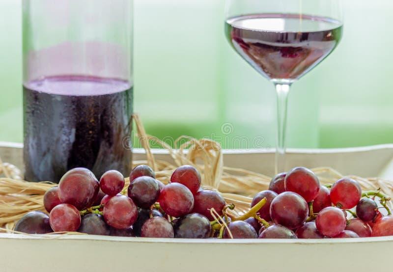Winw瓶、在一块土气板材的杯红葡萄酒和葡萄 库存照片