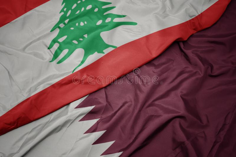 winzige bunte Flagge von Qatar und nationale Flagge von lebanon lizenzfreie stockfotografie