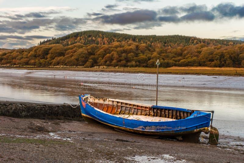 Wioślarska łódź kłama na borowinowym czekaniu dla przypływu wracać fotografia royalty free