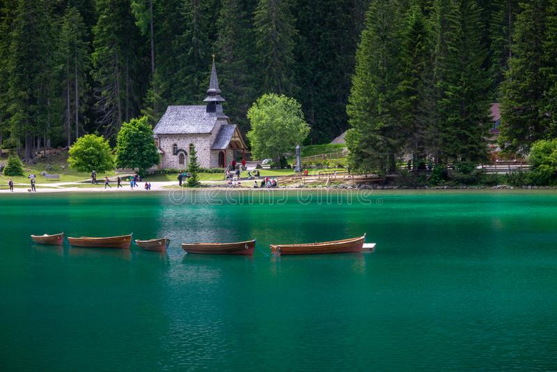 Wioślarskie łodzie przy Braies jeziorem z kościół w tle zdjęcia royalty free