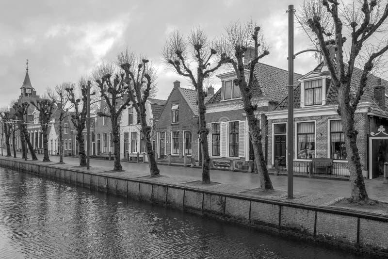 Wiosłuje z domami w czarny i biały fotografii w miedzy w Friesland, holandie obraz royalty free