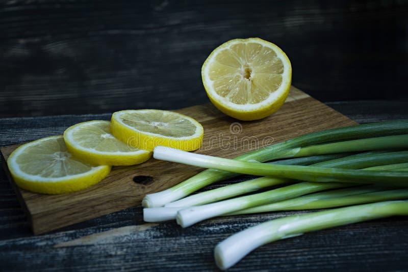 Wiosen cebule i przecinanie cytryna na ciemnym drewnianym tle zdjęcia royalty free