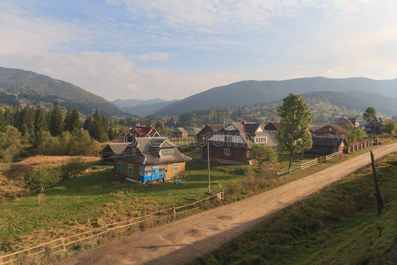 Wioska iluminuje słońcem i góry są dalekie carpathians zdjęcia stock