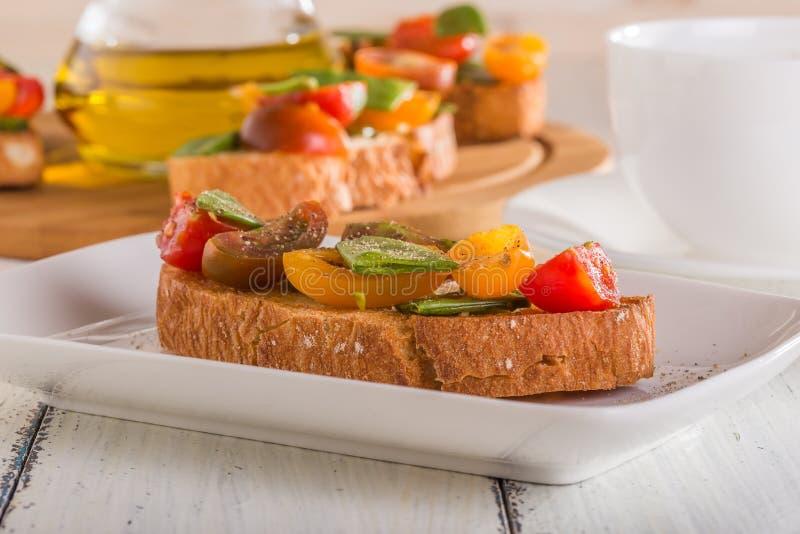 Wiosna Bruschetta z pomidorami i młodymi zielonymi grochami fotografia stock